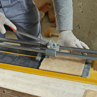 Laying Ceramic Tiles. Tiler cuts tile  manual cutter